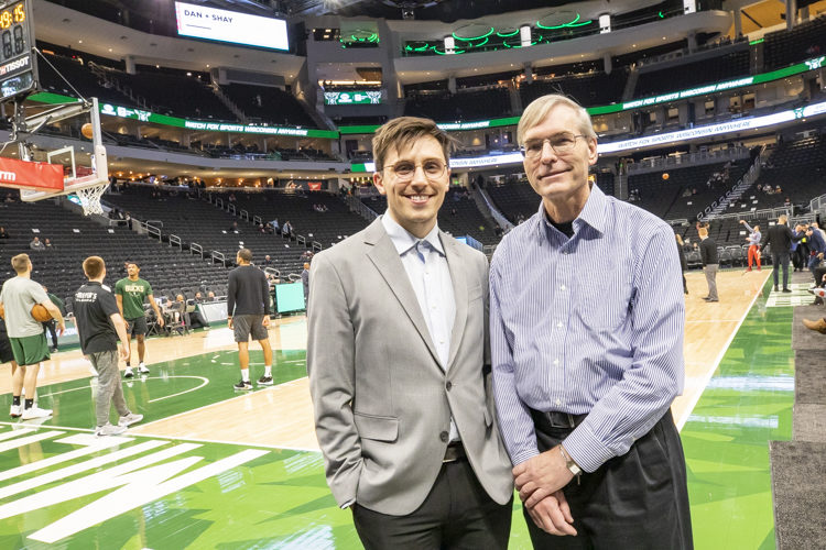 Two men pose on the sideline before a Milwaukee Bucks basketball game