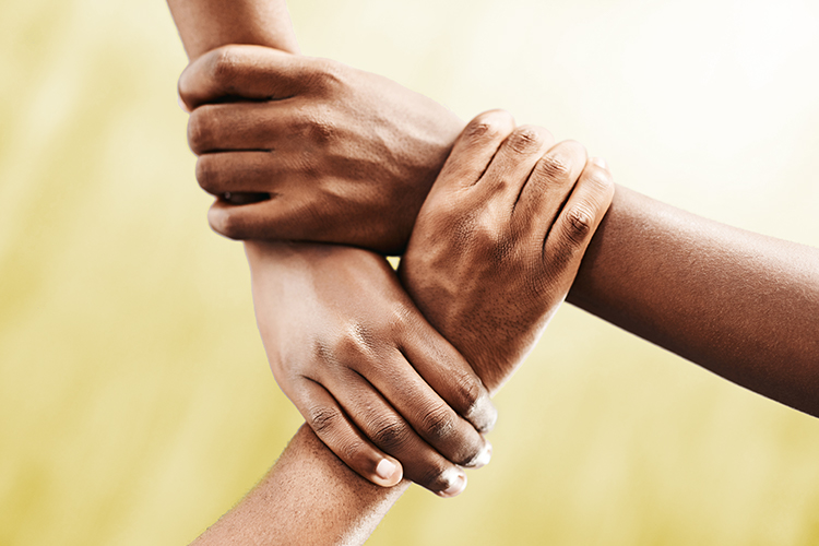 Photo of three hands, each holding another person's wrist