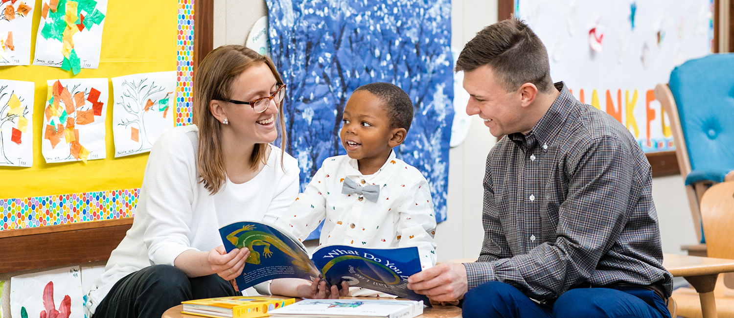 Two adults read to a child at a child care center