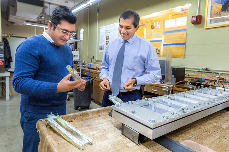 Two men work in a mechanical engineering lab
