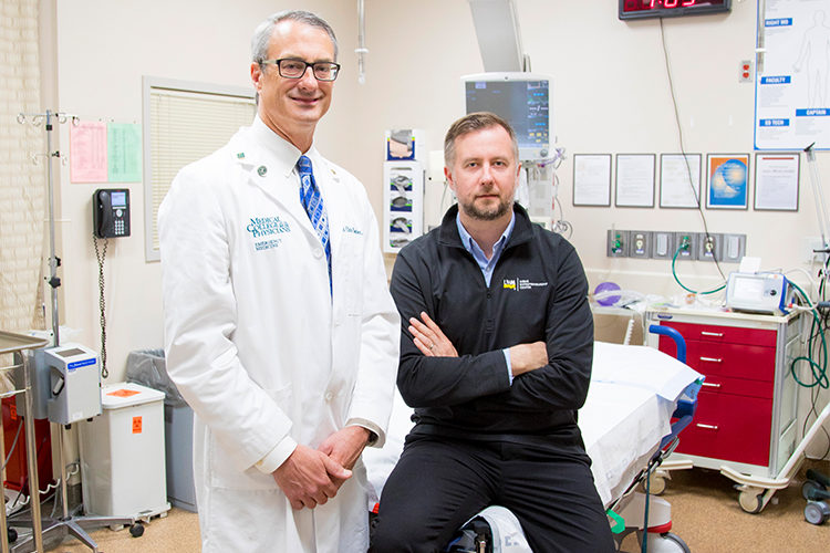 A doctor and professor pose for a picture in a hospital room