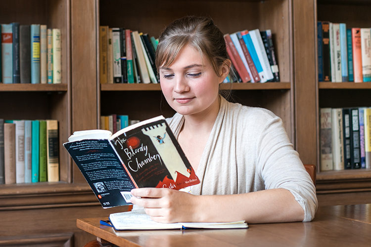 UWM student Bailey Flannery holding an open book