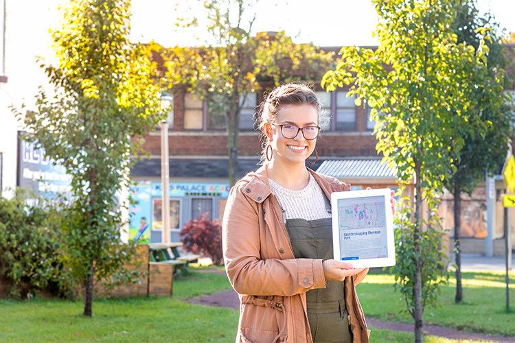 UWM undergrad researcher Bella Biwer holding interactive neighborhood map