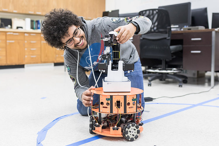 UWM undergrad researcher Isaac Ngui with omnidirectional robot