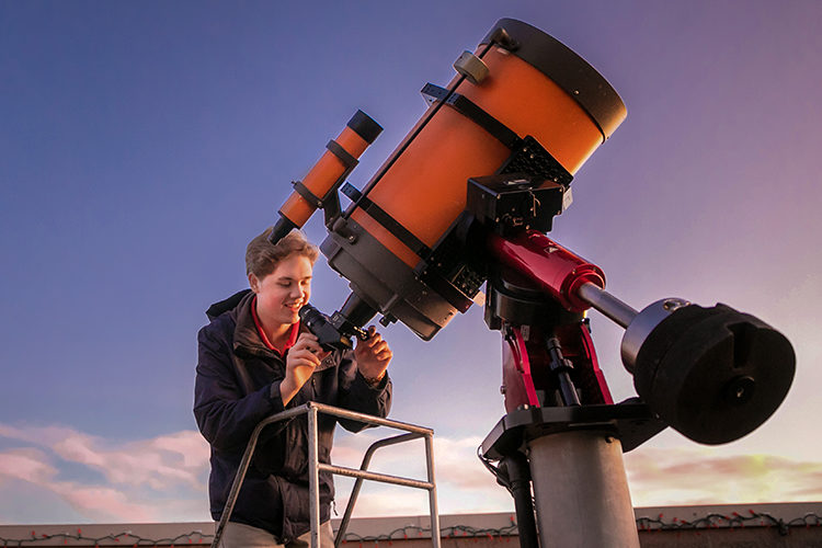 UWM student Nik Prusinski looking into a telescope