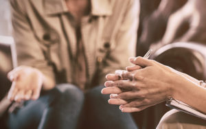 Image shows the hands of women in conversation.