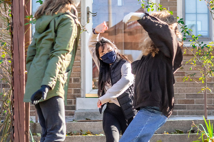 Three women dancing outside in a residential neighborhood
