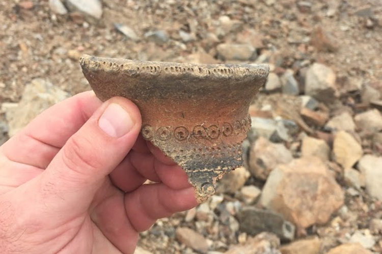 A hand holds a broken piece of pottery.