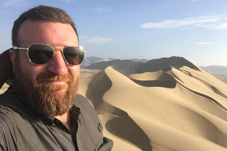 Man wearing sunglasses poses in front of a sand dune.