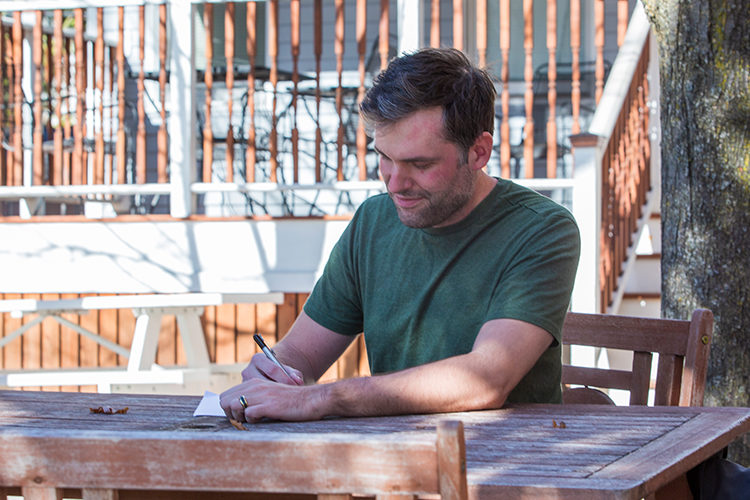Man writes at a table outside.
