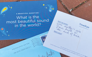Three blue postcards displayed on brick pavement