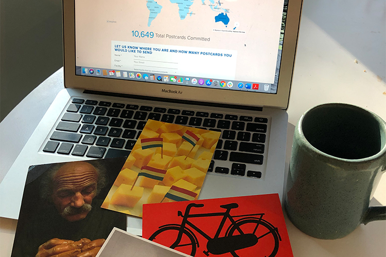 Two postcards, one with a bicycle illustration, in front of a computer screen