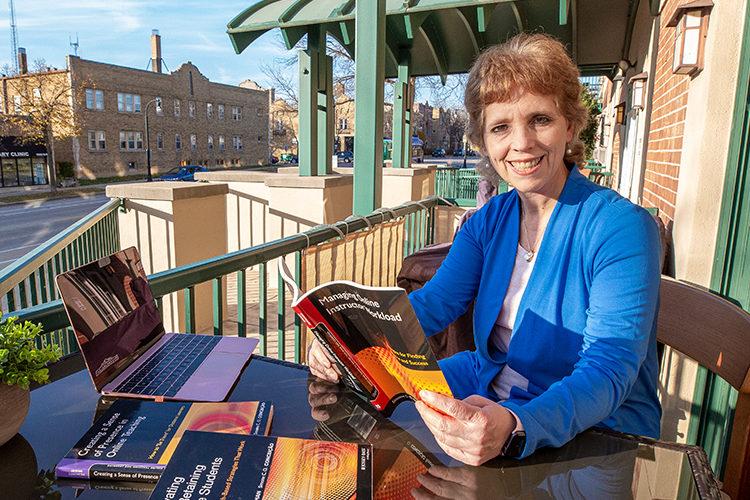 Conceição sits on a porch holding a book open.