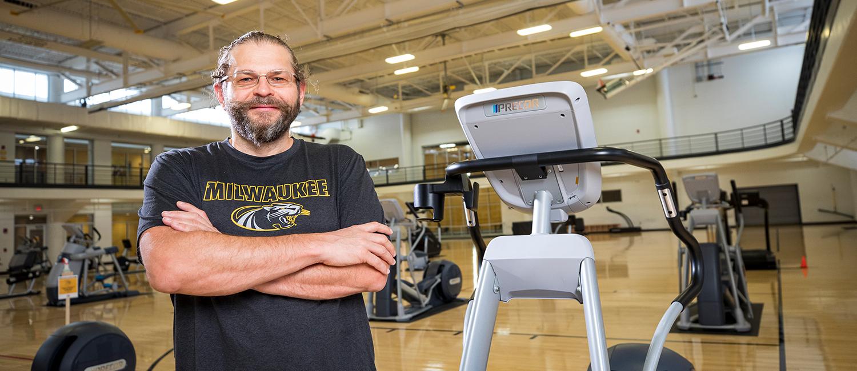 Konstantin Sobolev wearing UWM shirt and standing in gym near exercise equipment