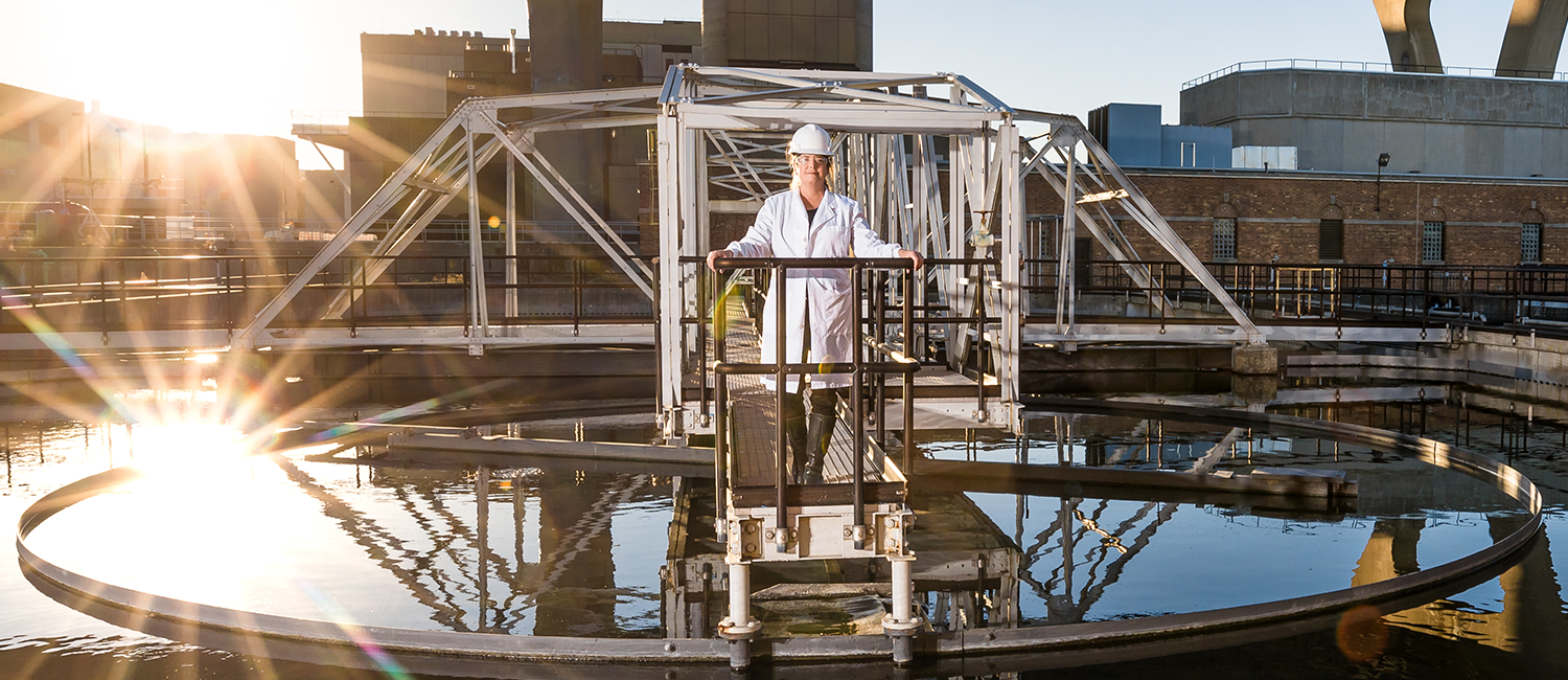 Sandra McLellan wearing a lab coat and hardhat standing over water treatment tank