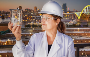 Sandra McLellan wearing a hard hat and holding a beaker with fluid in front of Hoen bridge