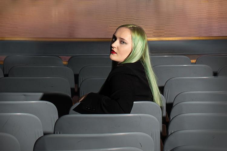 UWM undergrad researcher Xai Osa looking over shoulder in row of theatre seats
