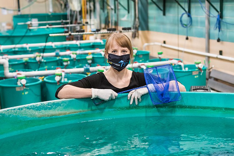 Undergrad researcher standing in front of research tank holding a blue net