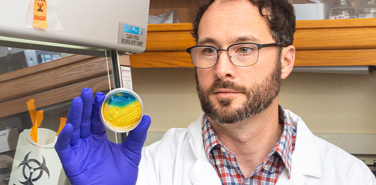 A researcher holds up a lab sample.