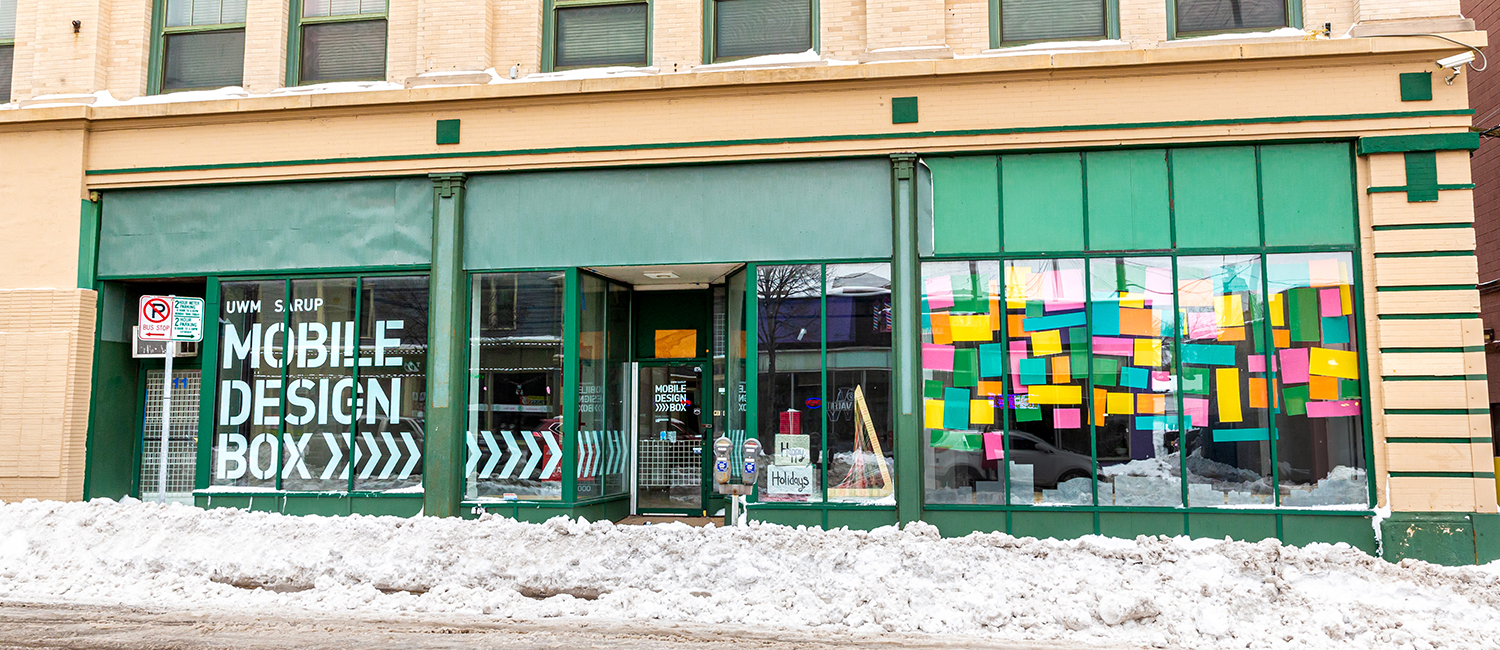 A storefront along a snow-plowed street.
