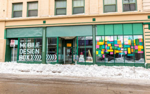 A storefront sits along a snow-plowed street.