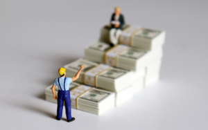 Illustration of two miniature figures of workers and cash..