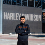 UWM student standing in front a of a large Harley Davidson sign.