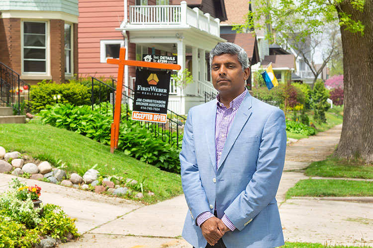 Man poses in front of a house for sale