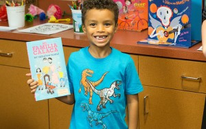 Proud winner of a book raffle at the Forest Home Library, this bilingual reader takes home a book in Spanish and English donated by the Center for Latin American and Caribbean Studies at UWM. (UWM Photo/Troye Fox)