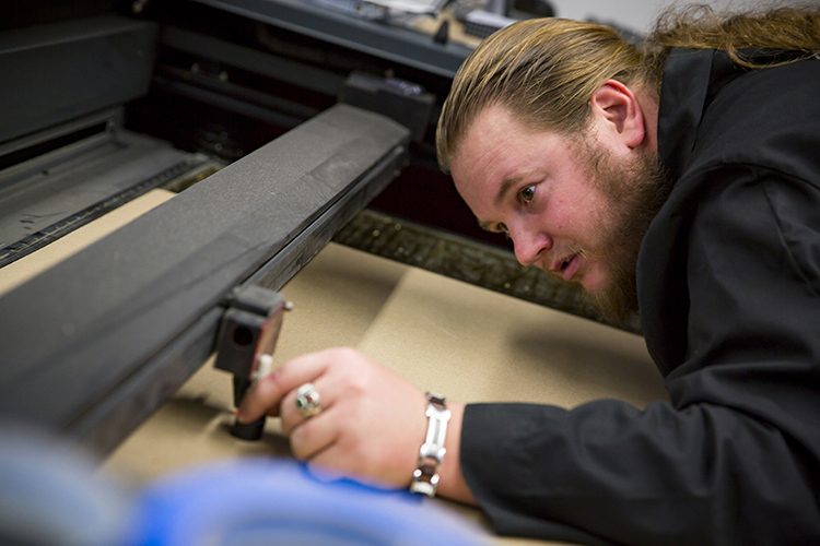 Engineering graduate student Joe Patzer gets to work in architecture's Rapid Prototyping Lab. (UWM Photo/Derek Rickert)