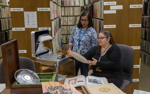 "Rebecca Littman (seated), head of the UWM Music Library, looks over ""The Rise & Fall of Paramount Records,"" volumes one and two. Joining her is Treshani Perera, a master's student in the library sciences/music history program. (UWM Photo/Troye Fox)"