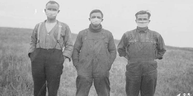 Historical black and white pandemic photo of three men wearing face masks