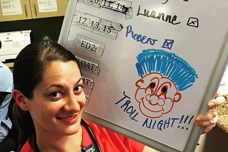 Amy Walia, RN to BSN Alumni poses near the Nurse's Desk with a Theme Night Drawing for Trolls Night