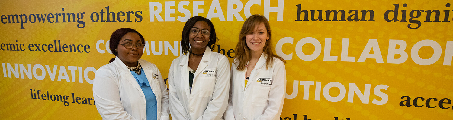 Three Nursing students in Nursing White Coats in Cunningham Hall in front of Gold Wall