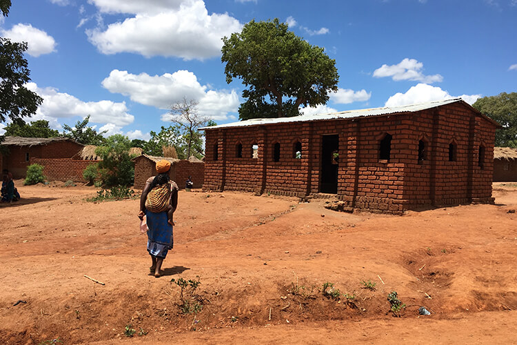 Malawi brick building with a mother carrying an infant on back - blue sky and puffy white clouds