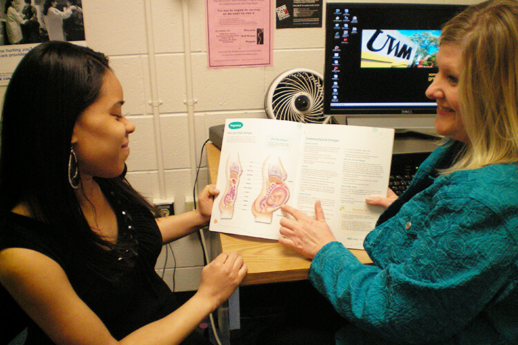 Michele Faltinson sits in a patient room with a mom to be holding a diagram of a pregnant mom