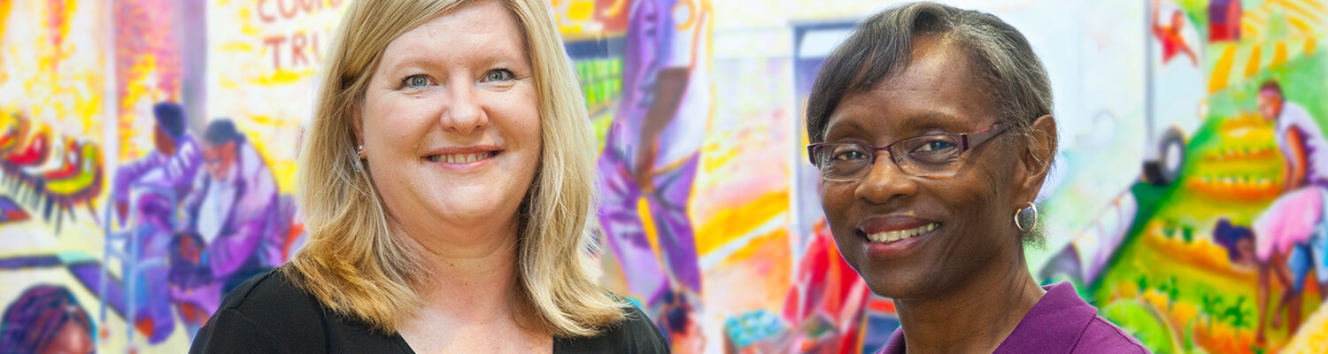 Two women smiling in front of of a colorful banner