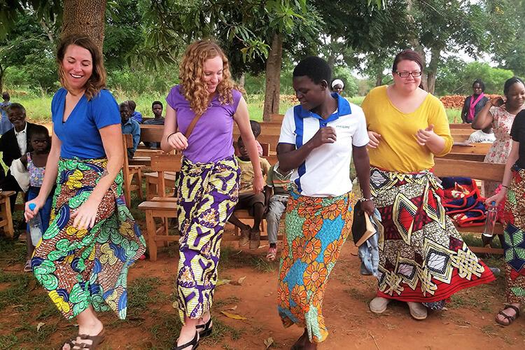 Alumni Victoria Sheer & Julie Kantor in Malawi dancing in African dresses