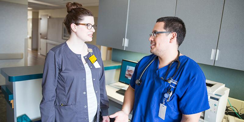 Nurse Faculty and Student Nurse talking at Hospital Nurse Station