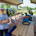Anne Dressel in Picnic Area of westlawn with bike repair in back
