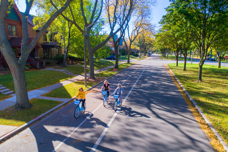 Three students riding bikes down boulevard on sunny day
