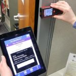 Photo of a practitioner measuring doorframe width using a laser ruler to determine accessibility