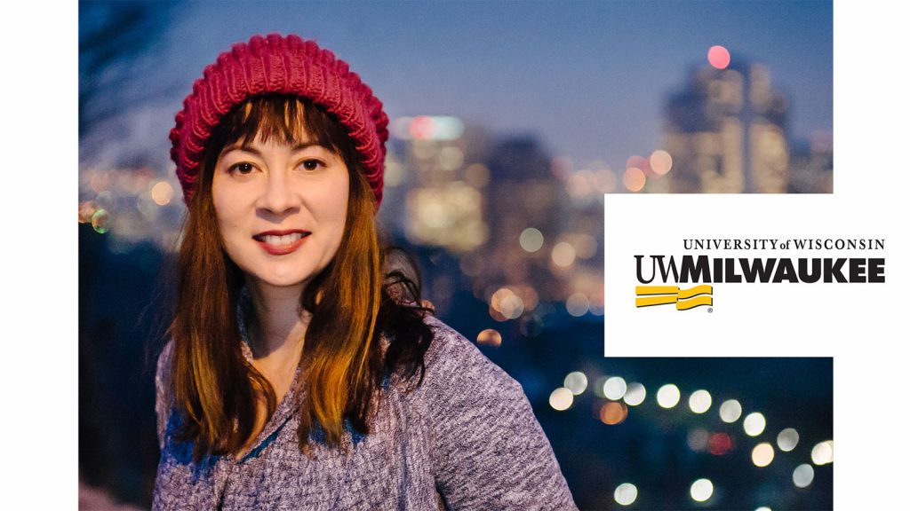 A woman in a purple sweatshirt and a read hat smiling. A UWM logo is in the right corner