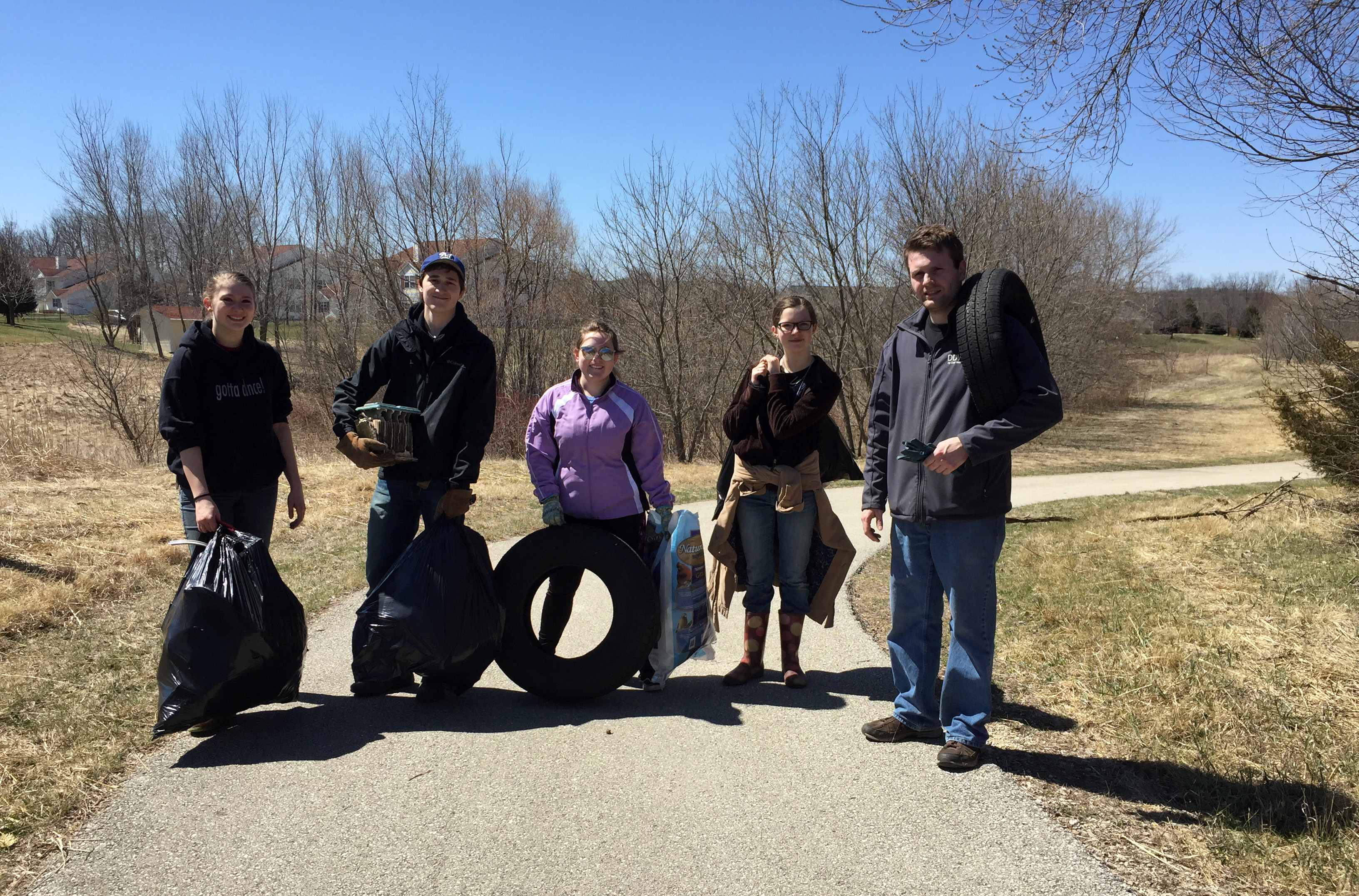 Five volunteers pose with garbage bags and tires collected during clean up event.