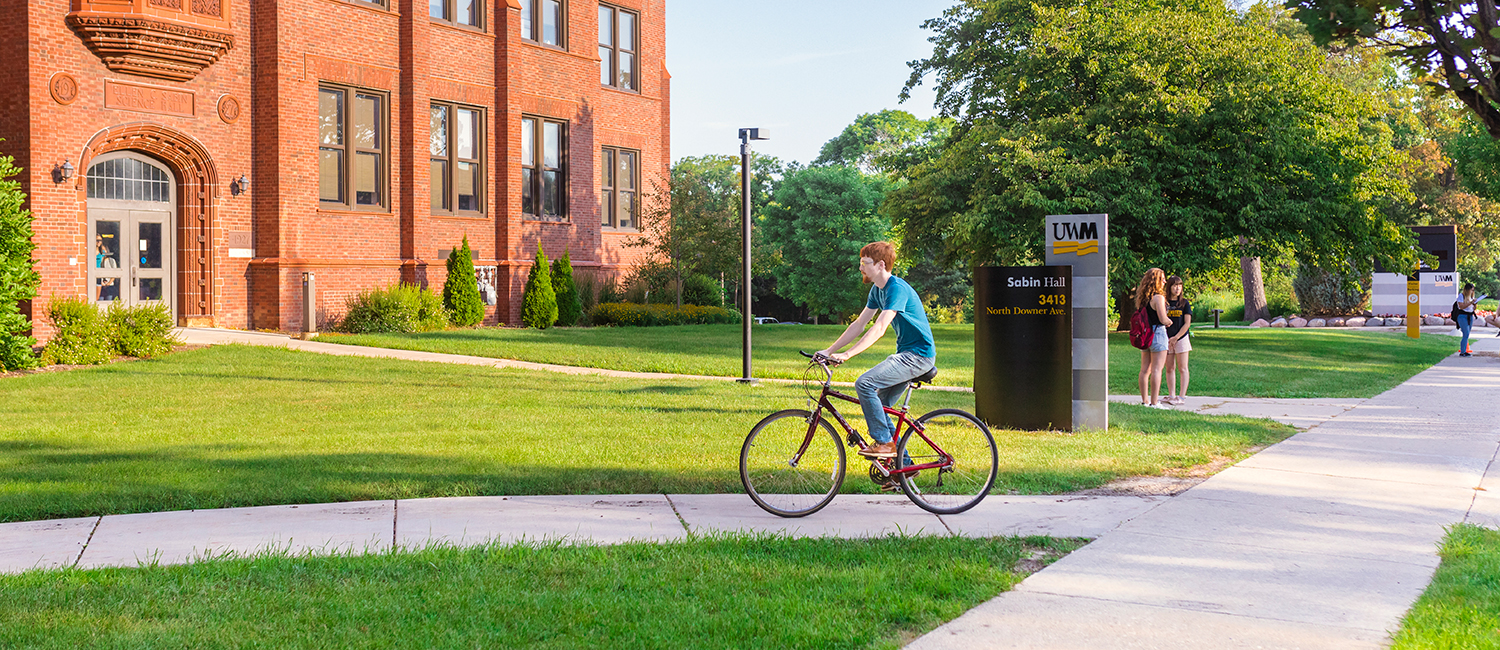 Student biking through campus near Sabin Hall