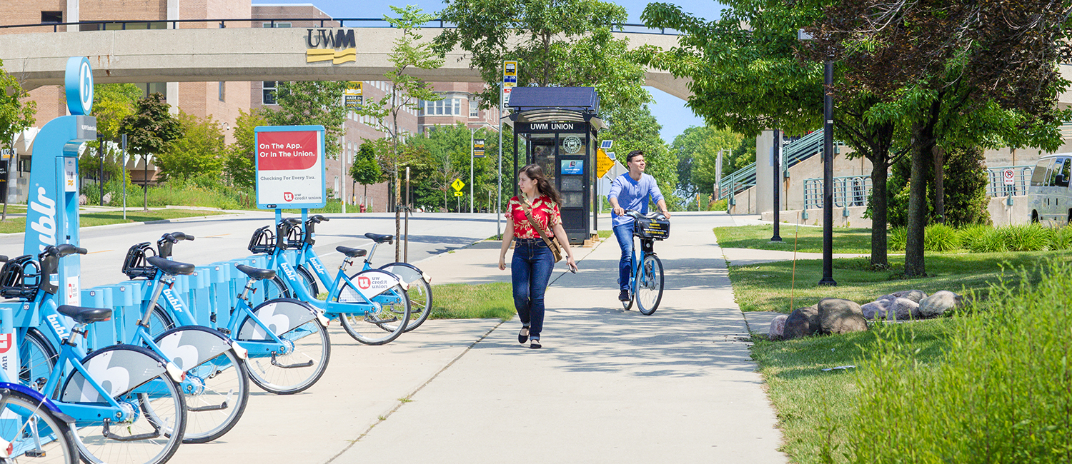 Student walking through campus and another on a Bublr bike
