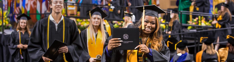 UWM student holding diploma at graduation