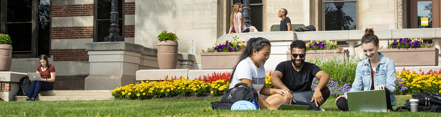 UWM students sitting outside in the grass