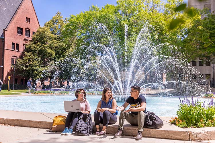 UWM students sit by the fountain on campus