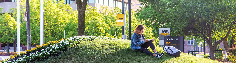 UWM student reading outside of Enderis Hall
